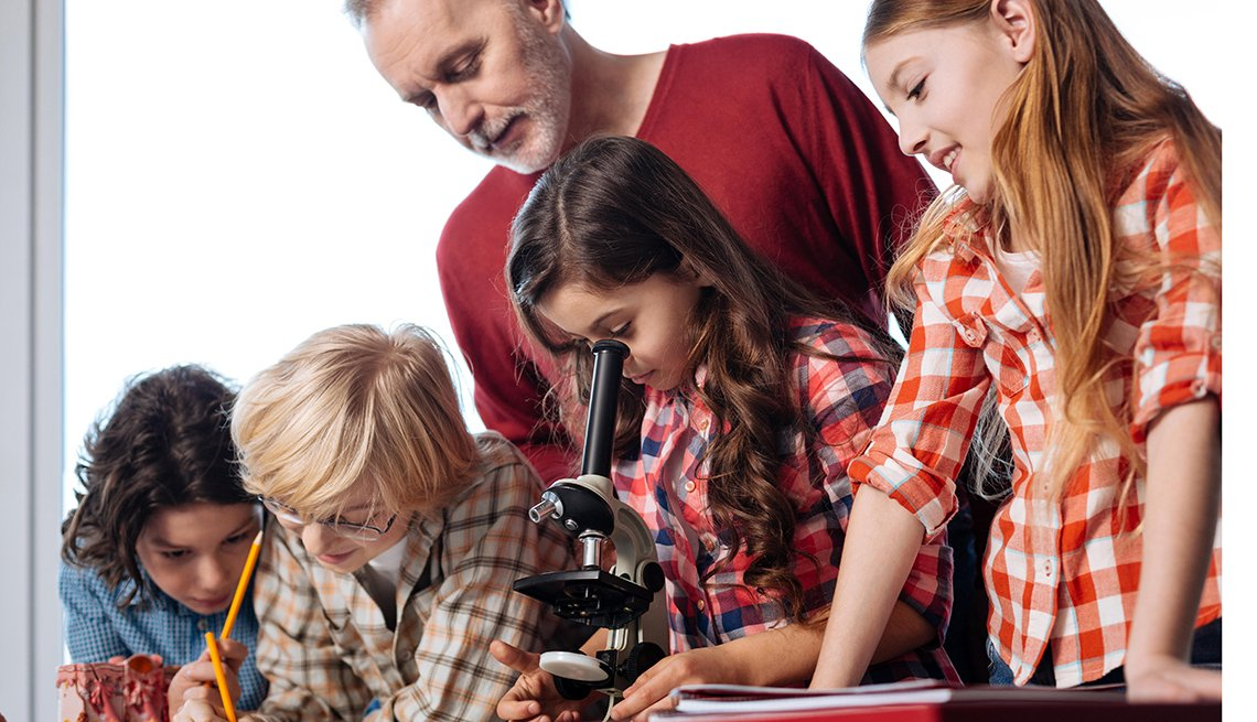 Children use microscope while man observes