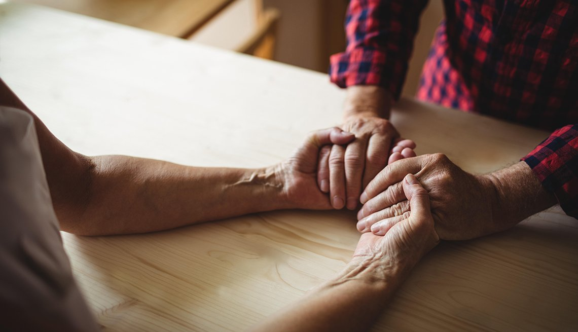 Caregiver holds hands of senior