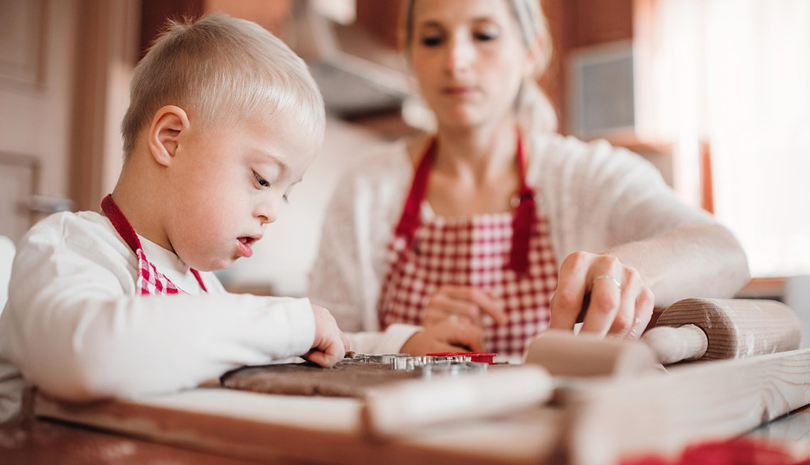 A female volunteer baking with a young boy who has down syndrome