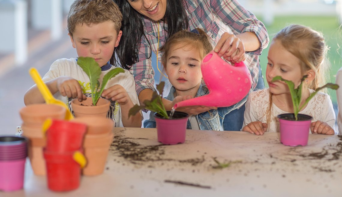 Woman helps children with gardening