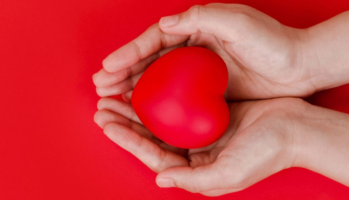 hands cupped holding a red heart
