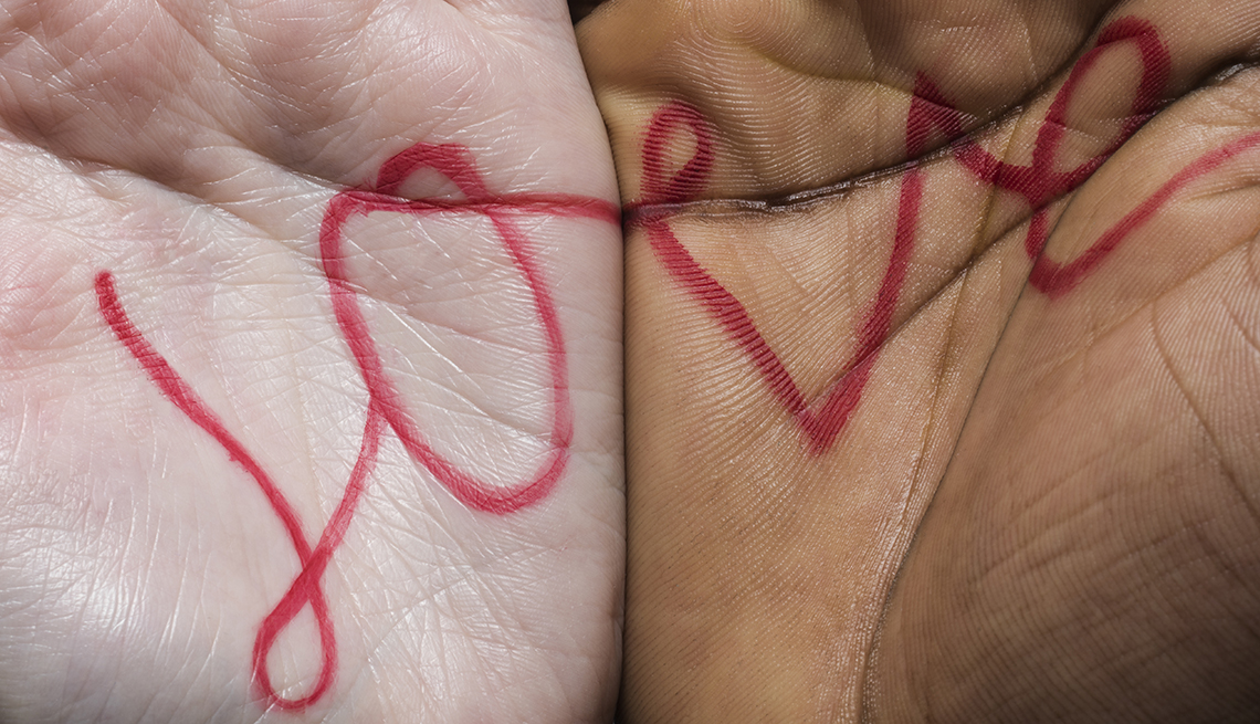 Close up of a caucasian hand next to an african american hand with the word love written across the palms in red marker.