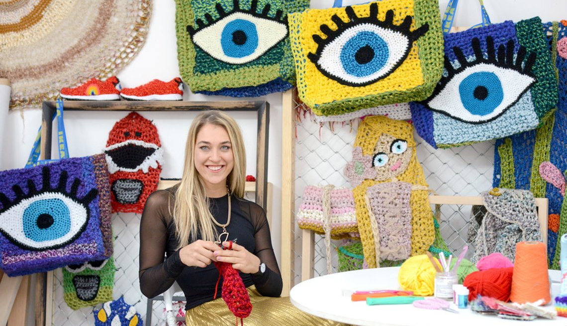 Young woman sits at table knitting colorful artwork.