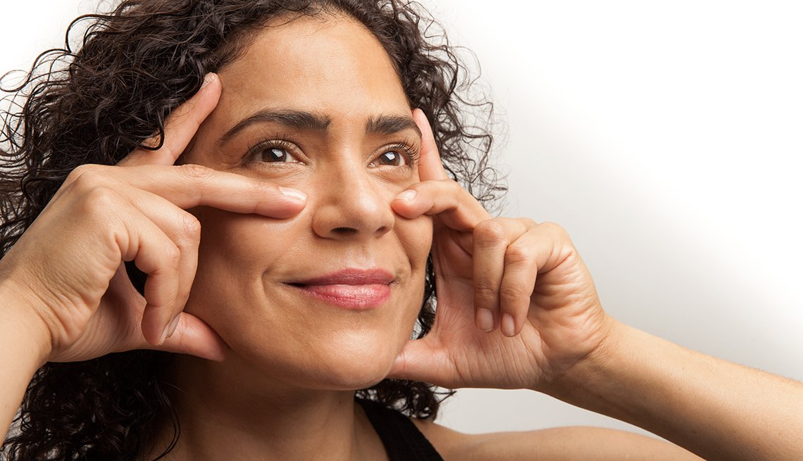Woman with hands on her cheeks doing face aerobics