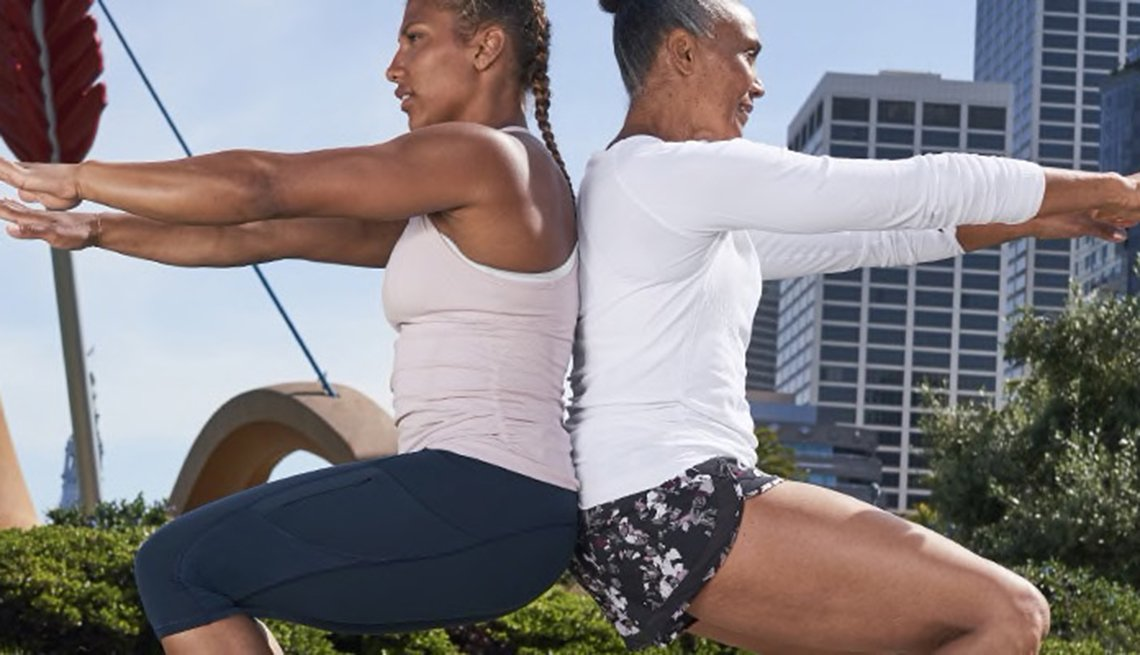 item 6 of Gallery image - Two woman exercising in a park, squatting back to back with arms outreached