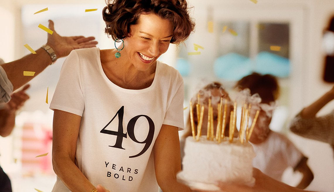 """item 8 of Gallery image - Woman smiling in front of a birthday cake wearing a shirt that say """"49 years bold"""""""