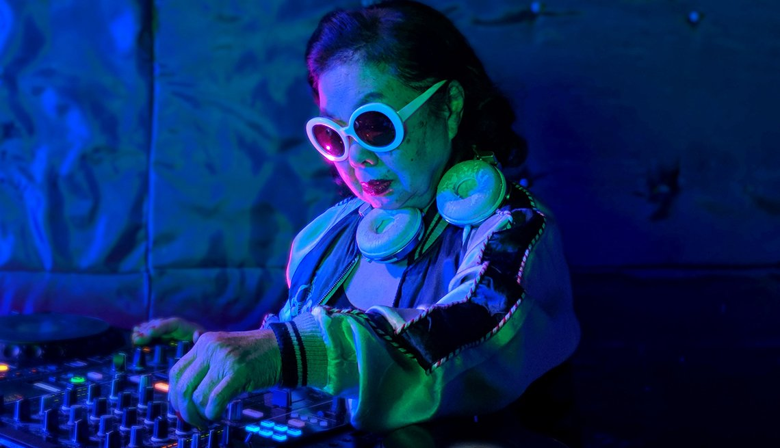 item 5 of Gallery image - Sumiko, a well know DJ in Tokyo, standing behind a mixing board with headphones around her neck and sunglasses on