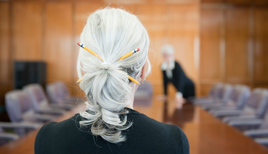Woman with grey ponytail working in a conference room