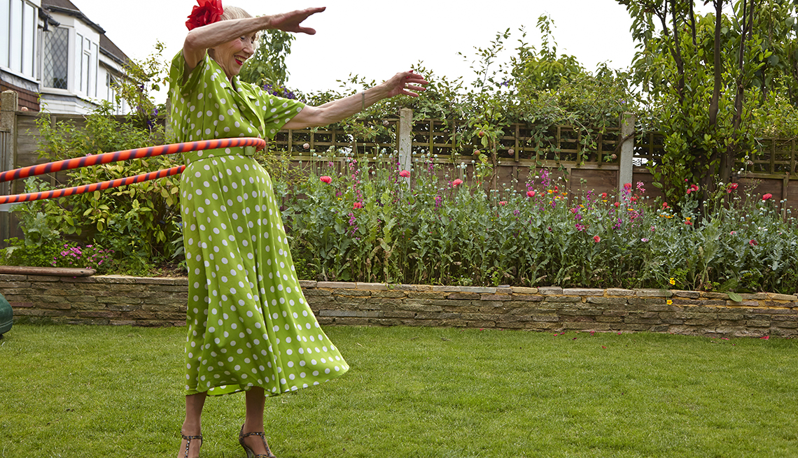 Older woman hula hooping in a garden