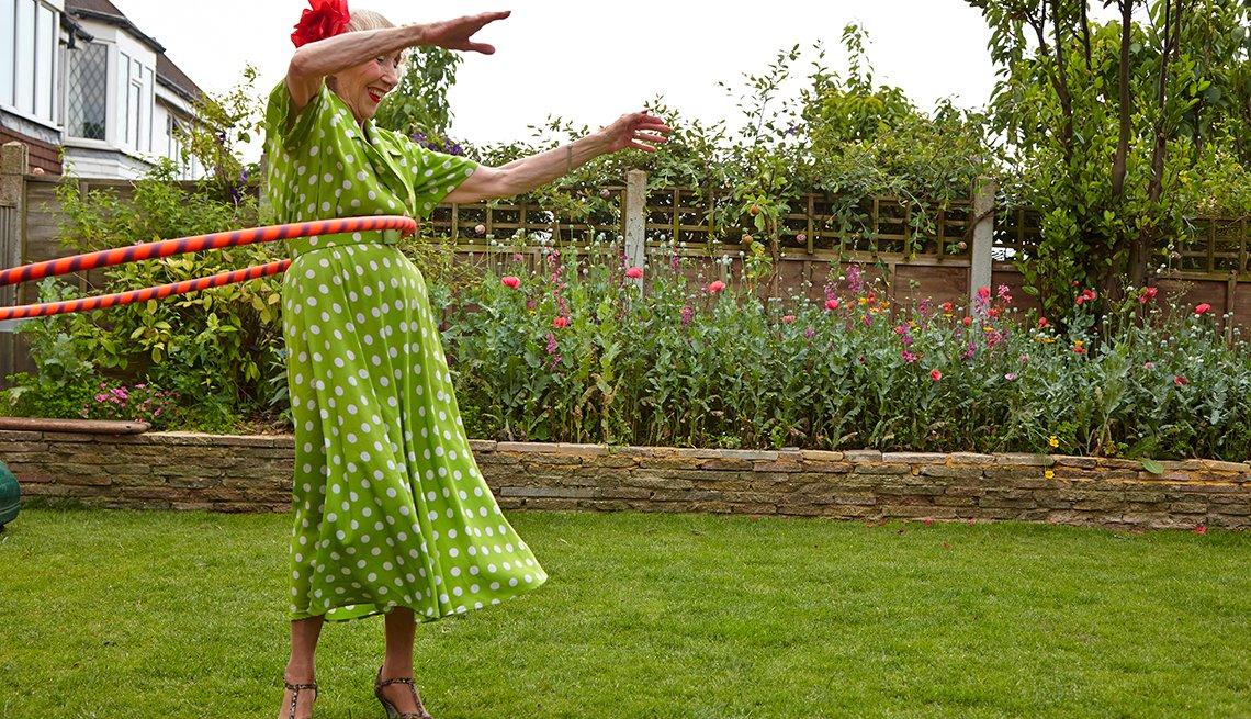 Older woman hula hooping in a garden