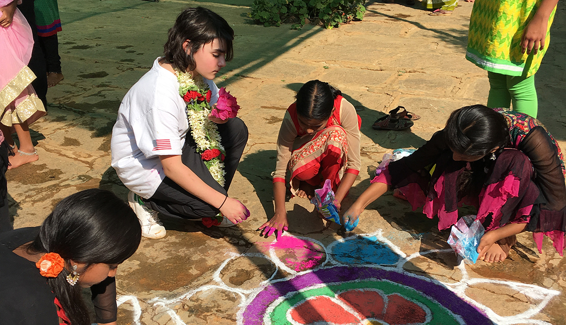 A  boy does chalk drawing with the young girls of the Baale Mane home.