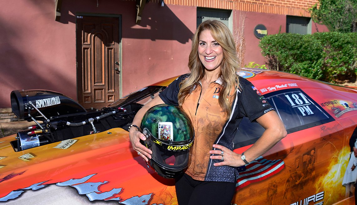 Drag racer Dina Parise in front of her race car and holding a helmet
