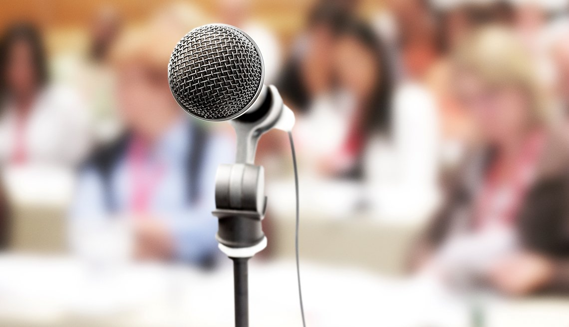 Close up on a vocal microphone in front of an out-of-focus audience at a meeting