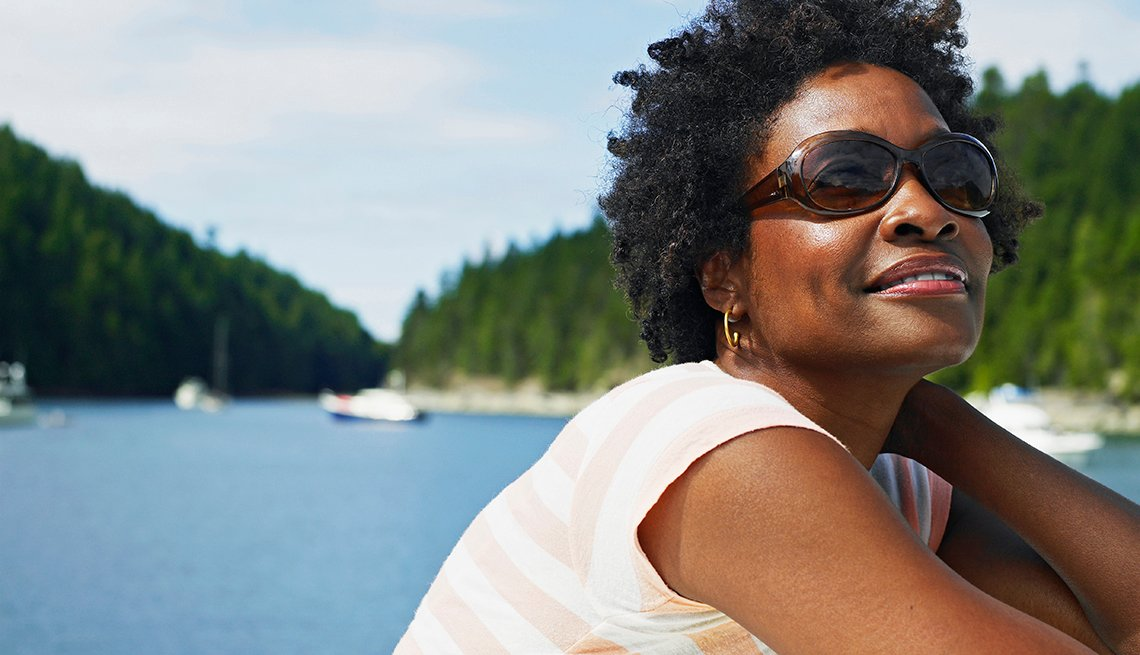 Close up of a woman wearing sunglasses to protect her eyes from the sun. A lake with boats is in the background