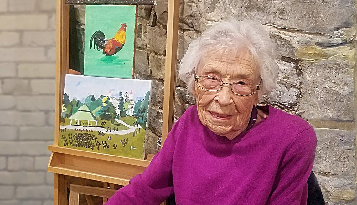 Helen Birdsey sitting in front of two of her paintings