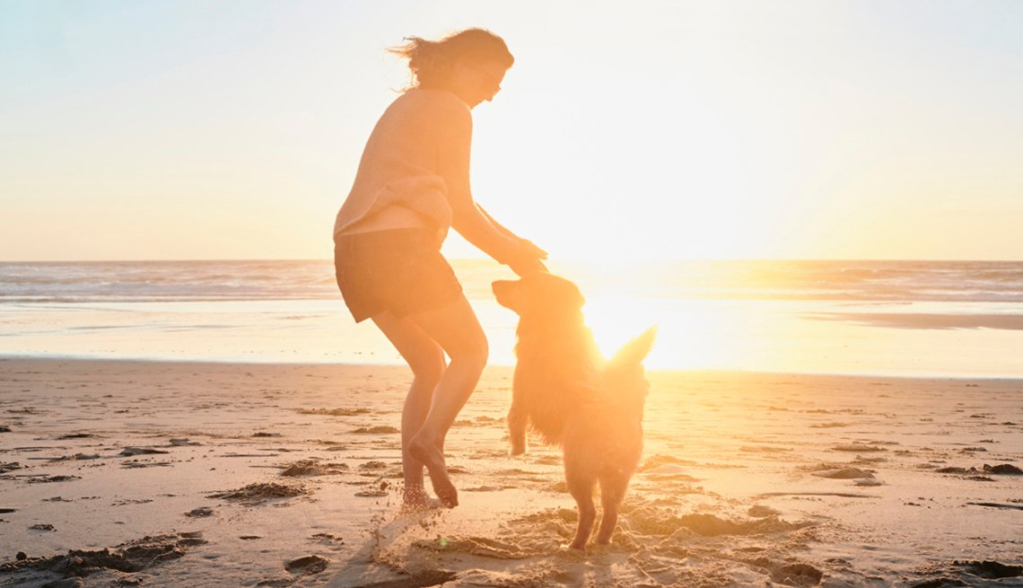 Woman playing with her dog on a beach at sunset