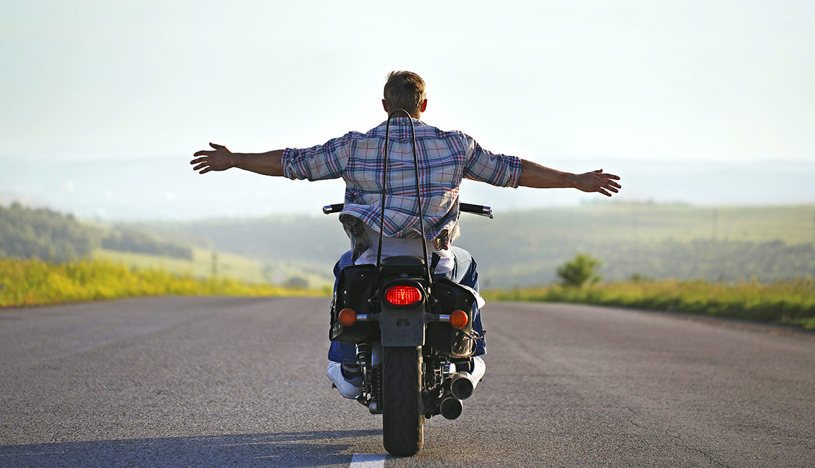 Man riding motorcycle with arms outstretched