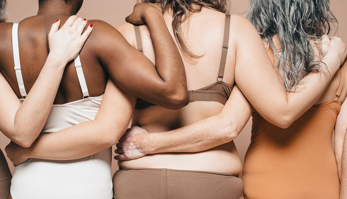 Five mixed races and ages women with their backs turned. They are holding hands and embracing each other. They wear underwear which show their normal and beautiful bodies