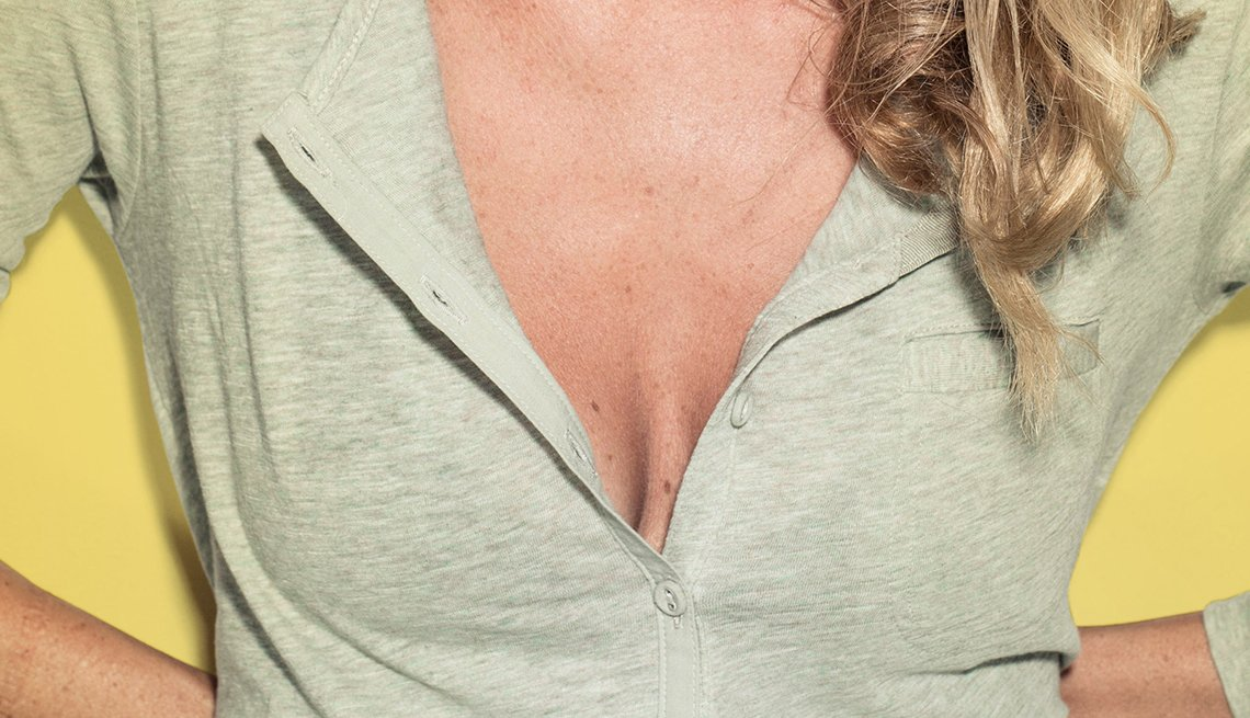 Woman with top buttons of blouse undone, showing cleavage
