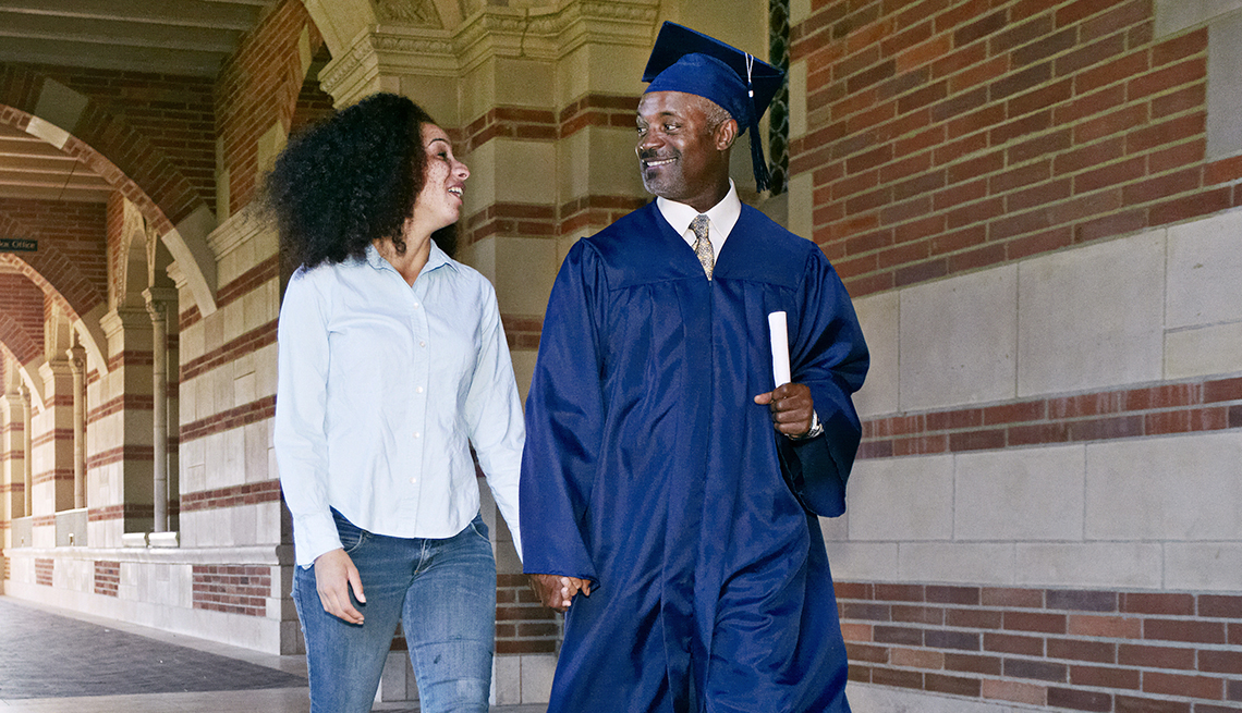 Man in a cap and gown walking, holding hands with his wife