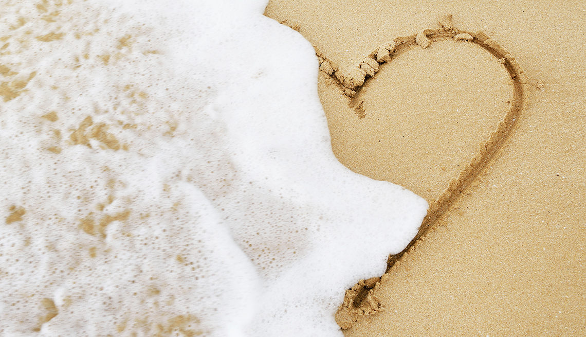 An ocean wave erasing a heart drawn in the sand