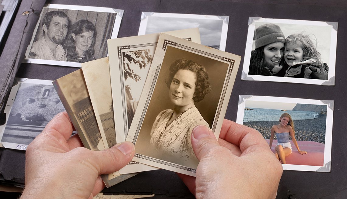 Hands holding old photographs of a woman with a old book of photographs in the background