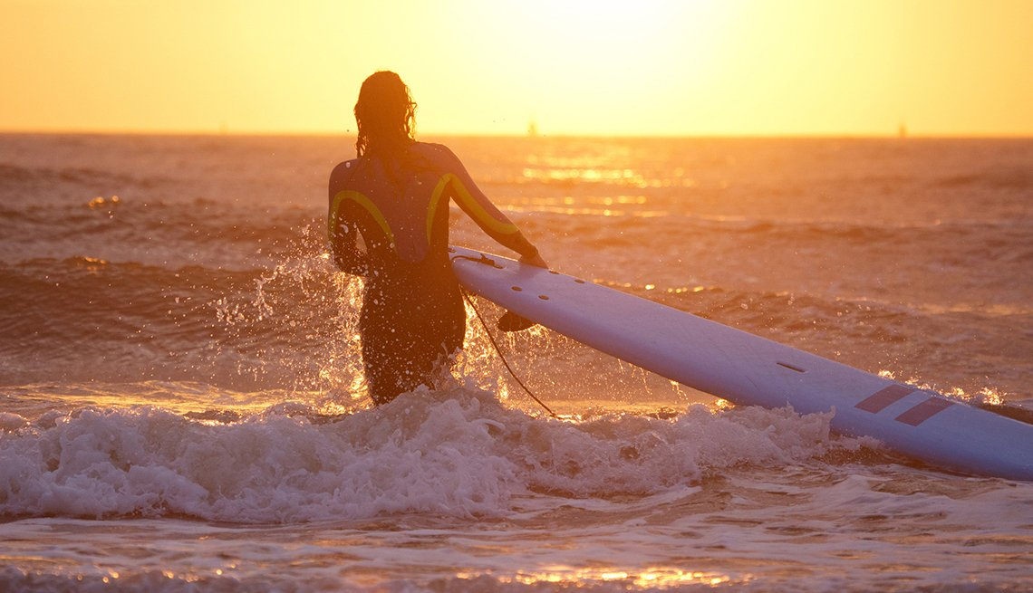 A female surfing alone at dusk