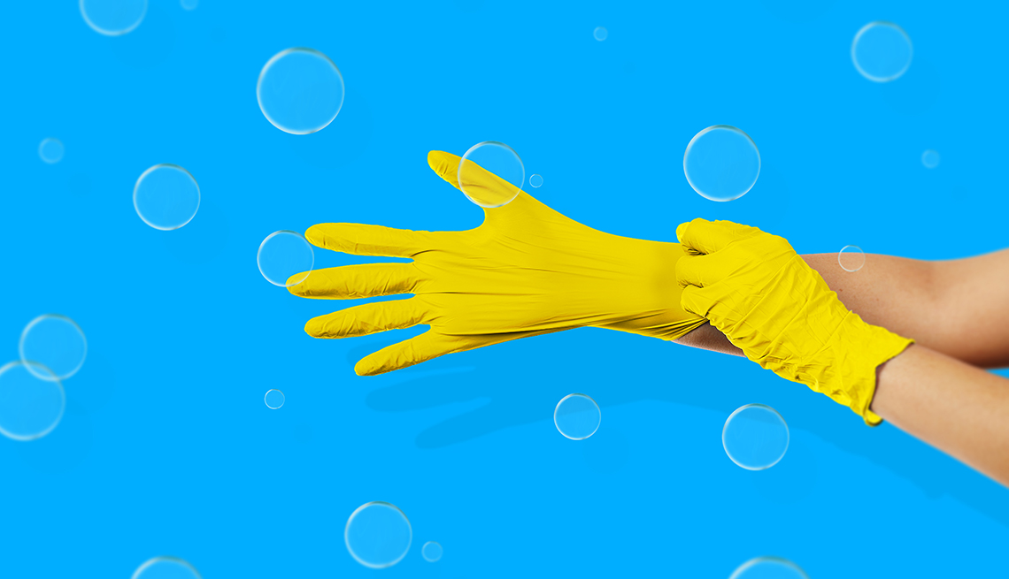 Close up of  a woman's hands pulling on a pair of yellow gloves