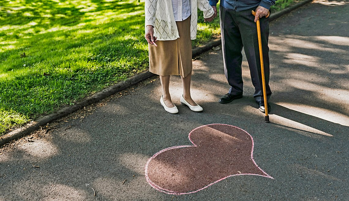 A woman and man with a cane standing next to a heart drawn on a sidewalk