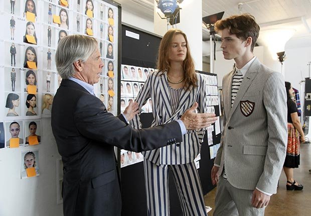 Tommy Hilfiger examines two designs from his Spring/Summer Collection 2013 on his models