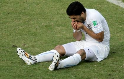 Luis Suárez reacciona mientras está sentado en el terreno de juego durante el partido de fútbol entre Italia y Uruguay en la Arena das Dunas en Natal, Brasil martes 24 de junio de 2014.