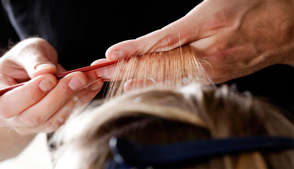 Estilista aplicando iluminaciones - Cuidado del cabello para hombres de 50 años o más