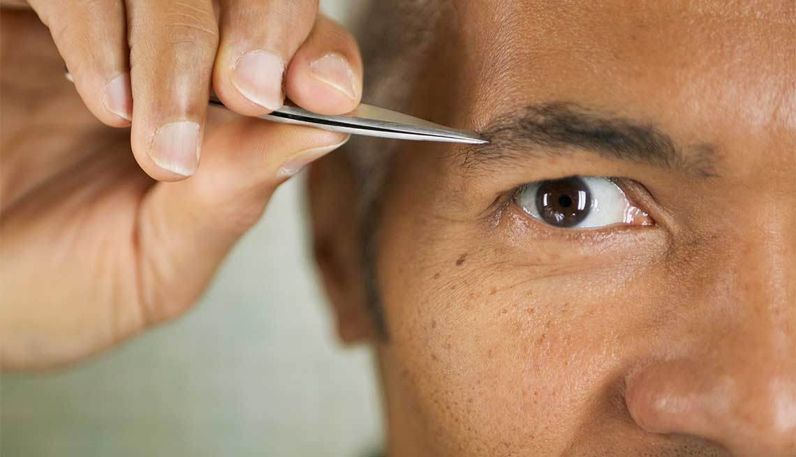 Hombre arreglándose las cejas con un depilador - Cuidado del cabello para hombres de 50 años o más