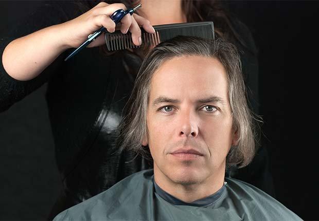 Estilista haciendo un corte a un hombre de cabello largo - Cuidado del cabello para hombres de 50 años o más