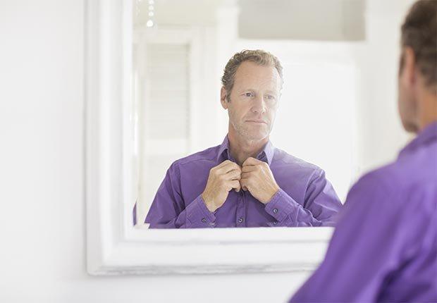 Hombre arreglándose la camisa en frente a un espejo en el baño - Cuidado del cabello para hombres de 50 años o más