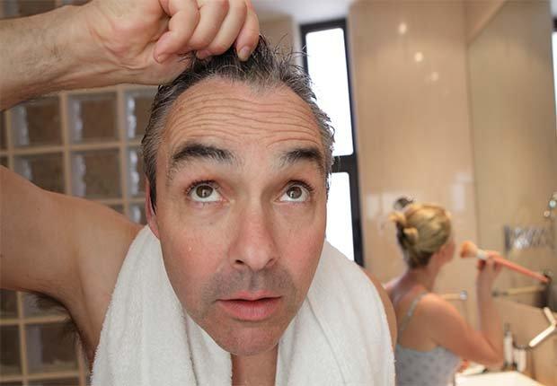 Hombre en el baño viendo su cabello en el espejo - Cuidado del cabello para hombres de 50 años o más
