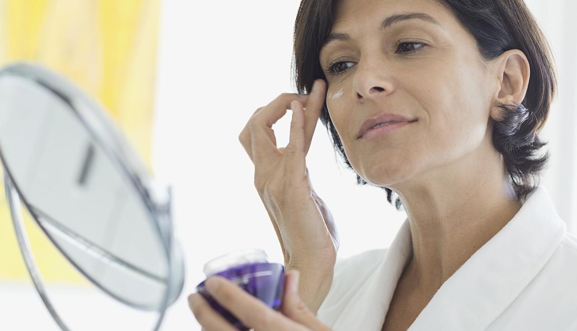 Maneras de verte 10 años más joven - Una mujer aplicando una crema en un rostro
