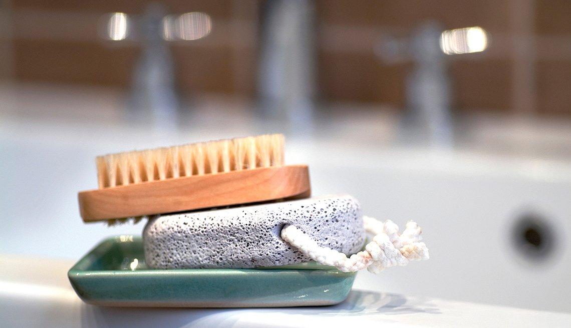 Maneras de verte 10 años más joven - Cepillo de aseo personal y piedra pomex en una bañera