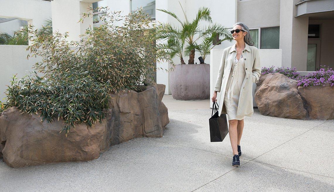 Maneras de verte 10 años más joven - Mujer caminando con un bolso en la mano