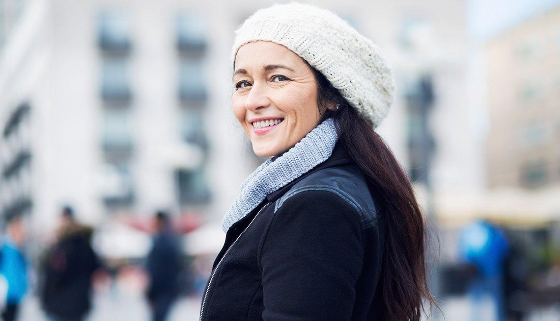 Mujer vestida con ropa de invierno y sonriendo porque cuida su piel en este temporada
