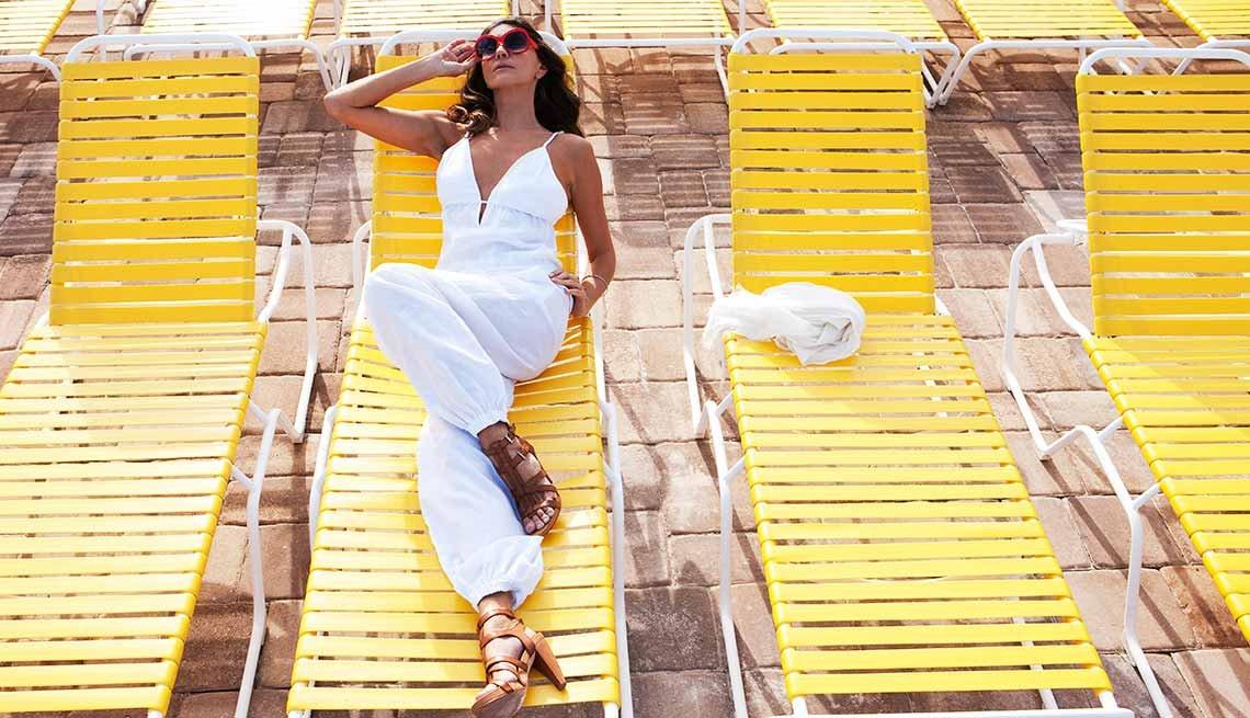 Mujer vestida de pantalón y blusa blanca con gafas para sol, posando ante la cámara recostada en un asoleador - Abuelas con glamour en la Florida