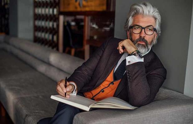 Hombre mayor en traje de corbata sentado en un sofá con un libro de apuntes y un lapicero - Secretos de moda de hombres sexy