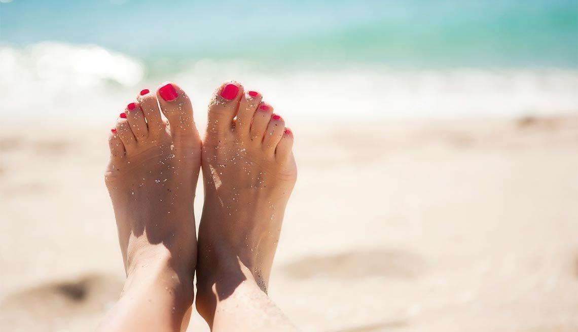Los pies de una mujer en una playa reflejan la salud y los cuidados a tener en un salón de uñas