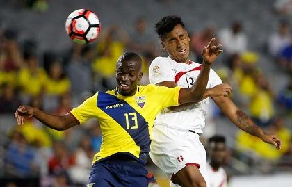 El peruano Renato Tapia y el ecuatoriano Enner Valencia disputan un balón.