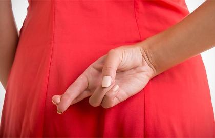 Una mujer cruzando los dedos en su espalda.