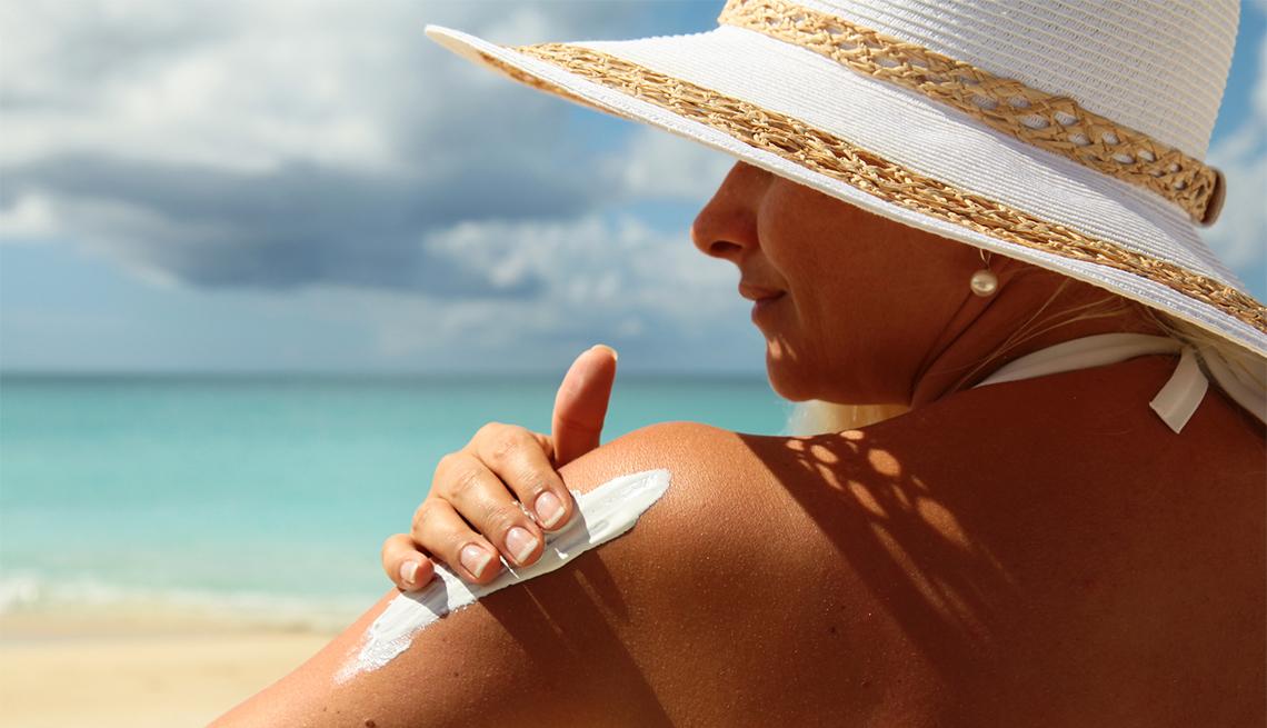 Mujer en una playa colocándose bloqueador solar