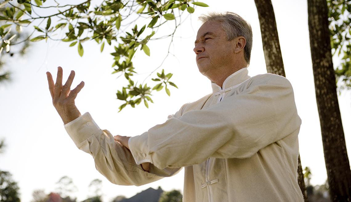 Hombre mayor practicando Tai Chi en un bosque