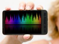 Mujer mostrando un mp3 contemporáneas de teléfonos inteligentes, aplicaciones de reconocimiento de música