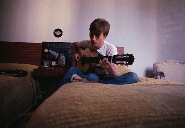 John Lennon tocando su guitarra en la habitación de hotel en 1966, Beatlemanía.