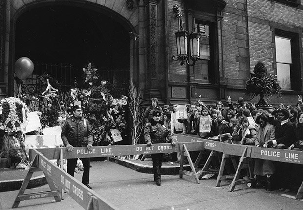 La policía de Nueva York mantiene a los espectadores detrás de la arcada cerrada del edificio Dakota, donde fue asesinado John Lennon, Beatlemanía.
